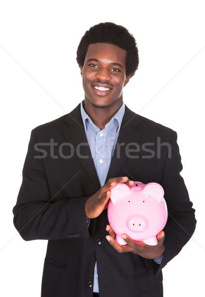 African Businessman Holding Piggybank Stock photo © AndreyPopov