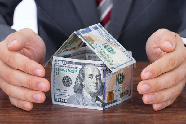 Businessman Sheltering House Made With Bank Notes Stock photo © AndreyPopov