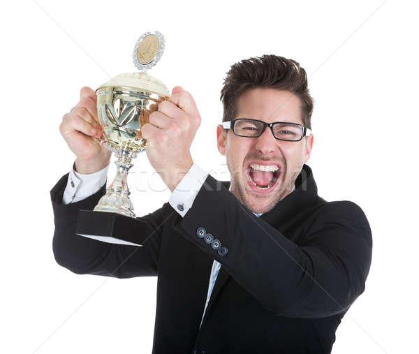 Sikeres fiatal üzletember tart trófea portré Stock fotó © AndreyPopov