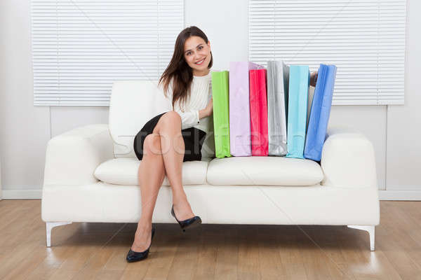 üzletasszony tarka bevásárlótáskák ül kanapé portré Stock fotó © AndreyPopov