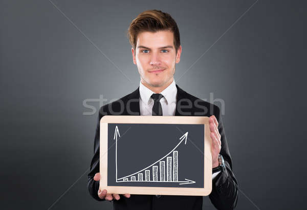 Businessman Holding Slate With Growing Bar Graph Stock photo © AndreyPopov