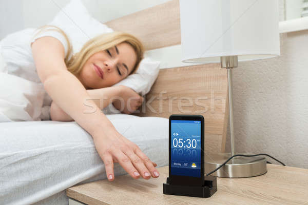 Woman Snoozing Alarm On Mobile Phone Screen Stock photo © AndreyPopov