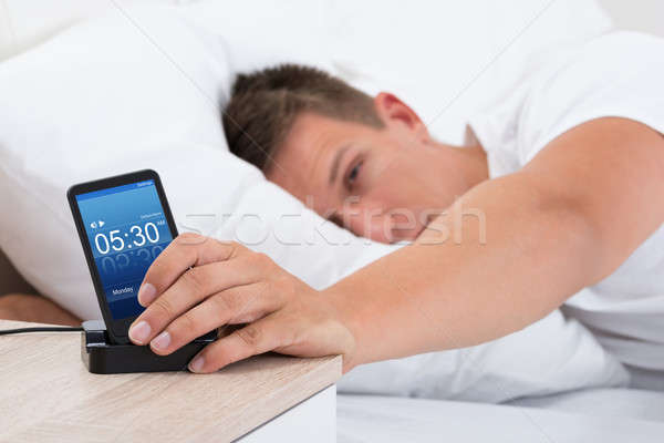 Man Snoozing Alarm Clock On Cell Phone Stock photo © AndreyPopov