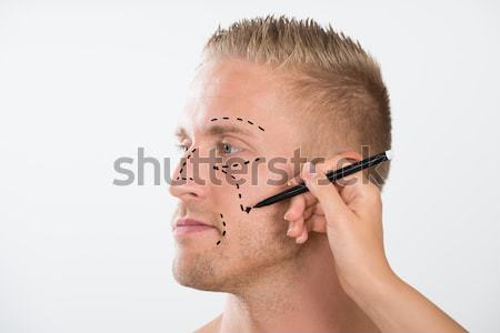 Person's Hand Drawing Correction Line With Pen Near Man's Eyes Stock photo © AndreyPopov