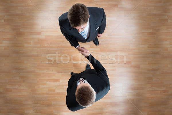 Empresários aperto de mãos escritório diretamente acima tiro Foto stock © AndreyPopov
