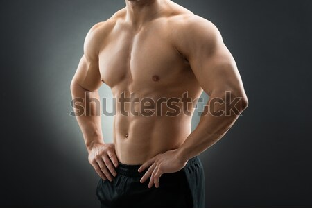 Muscular Man Standing With Hands On Hip Stock photo © AndreyPopov