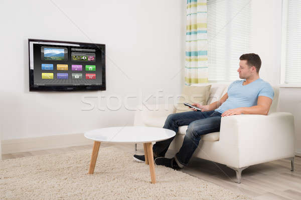 Stock photo: Man With Remote Control Watching Television At Home