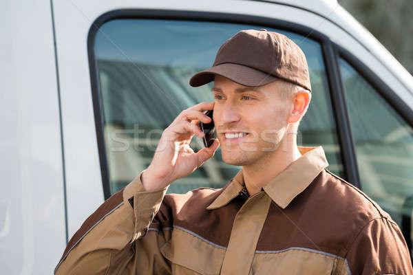 Mosolyog futár mobiltelefon teherautó portré autó Stock fotó © AndreyPopov