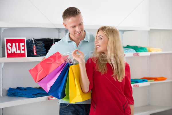 Man Looking At Woman Carrying Shopping Bags Stock photo © AndreyPopov