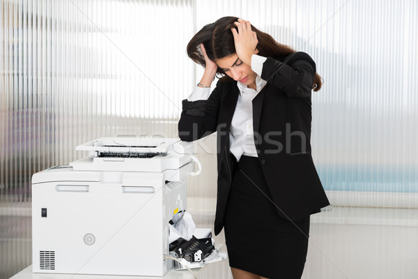 Irritated Businesswoman Looking At Paper Stuck In Printer Stock photo © AndreyPopov