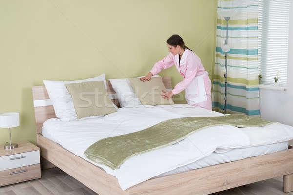 Vrouwelijke huishoudster kussen bed jonge kamer Stockfoto © AndreyPopov