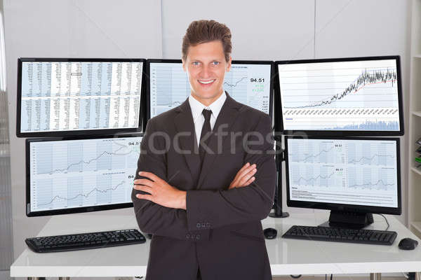 Broker Standing Arms Crossed Against Multiple Screens Stock photo © AndreyPopov