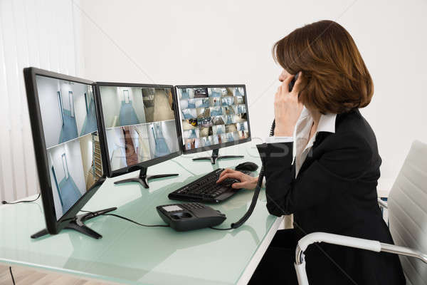 Female Operator Looking At Multiple Camera Footage On Computers Stock photo © AndreyPopov