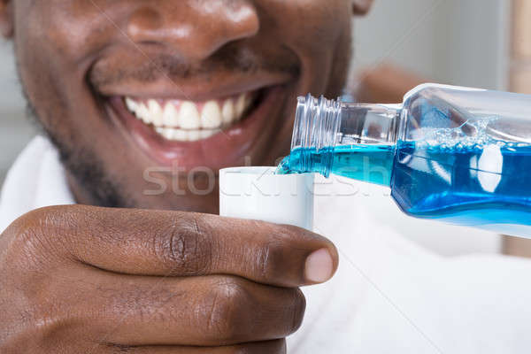 Close-up Of A Man Pouring Mouthwash Into Cap Stock photo © AndreyPopov