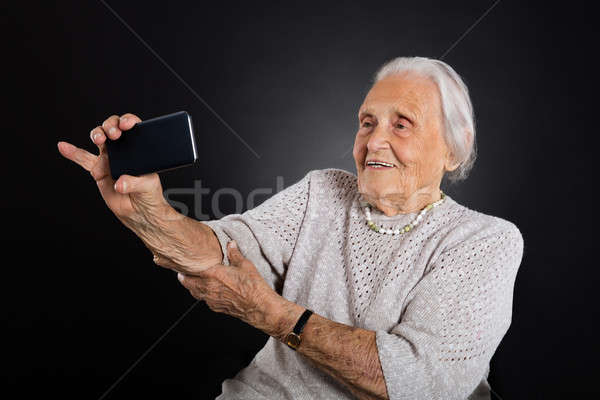 Aîné femme smartphone portrait souriant Photo stock © AndreyPopov