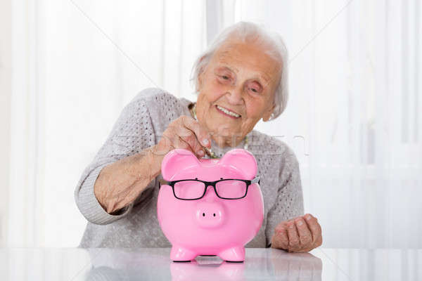 Senior Woman Inserting Coin In Piggybank Stock photo © AndreyPopov