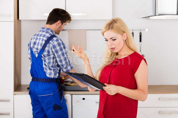Frustrated Woman Looking At Bill On Clipboard In Kitchen Stock photo © AndreyPopov