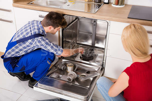 Woman Looking At Repairman Repairing Dishwasher Stock photo © AndreyPopov