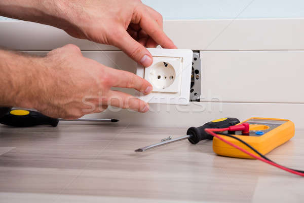 Person's Hand Installing Socket On Wall Stock photo © AndreyPopov