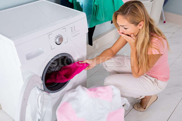 Woman Looking At Stained Cloth In Washing Machine Stock photo © AndreyPopov
