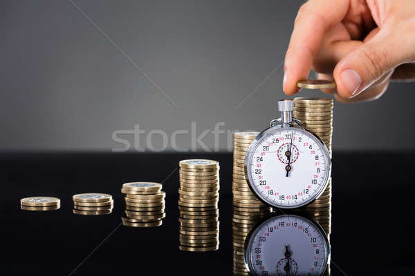 Person Stacking Coins On Desk Near Stopwatch Stock photo © AndreyPopov