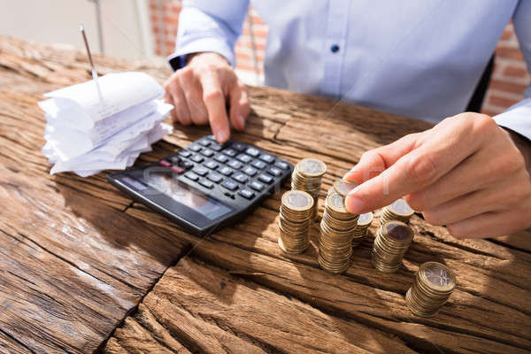 Person Counting Coins Using Calculator Stock photo © AndreyPopov