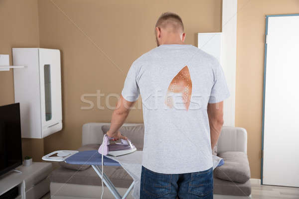 Rear View Of A Man Ironing Cloth Stock photo © AndreyPopov