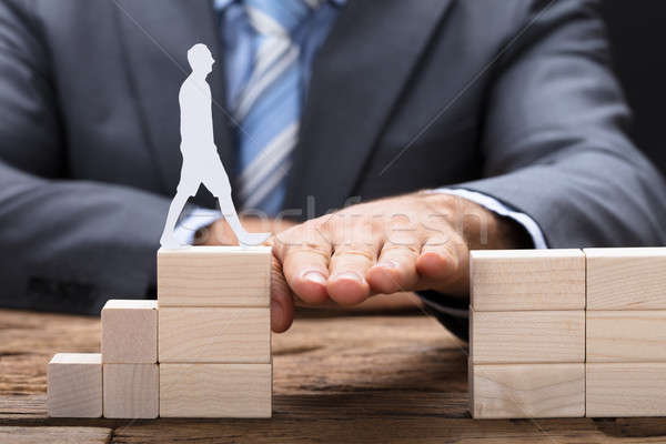 Hand Between Blocks With Paperman Walking On It Stock photo © AndreyPopov