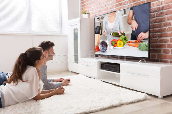 Happy Couple Watching Recipe On Television Stock photo © AndreyPopov