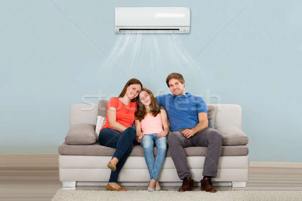 Family Sitting On Sofa Under Air Conditioning Stock photo © AndreyPopov