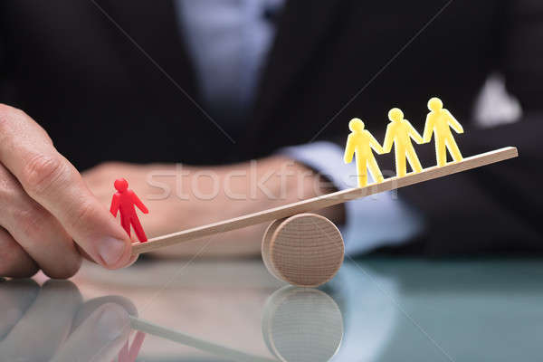 Businessperson Showing Imbalance Between Figures On Seesaw Stock photo © AndreyPopov