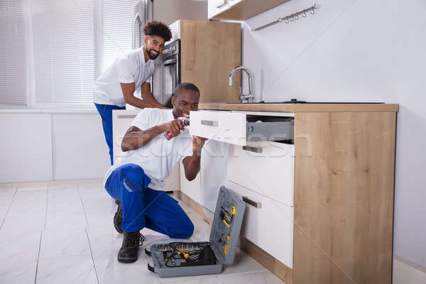 Repairmen Fixing The Wooden Cabinet In The Kitchen Stock photo © AndreyPopov