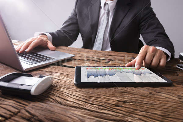 Stock Market Broker Analyzing Graph On Digital Tablet Stock photo © AndreyPopov