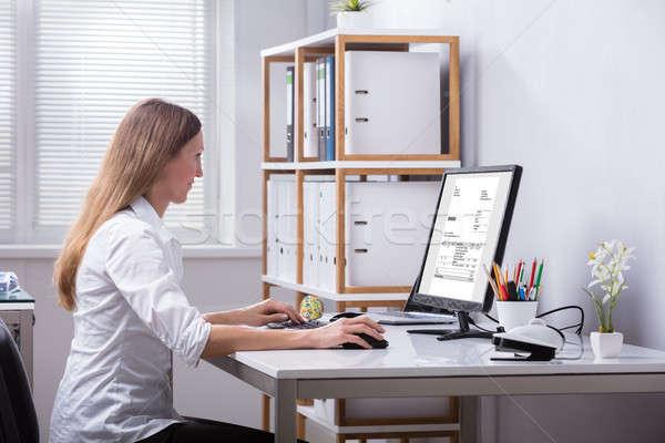 Businesswoman Checking Invoice On Computer Stock photo © AndreyPopov