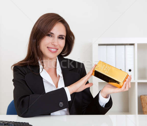 Businesswoman Holding Gold Bar Stock photo © AndreyPopov