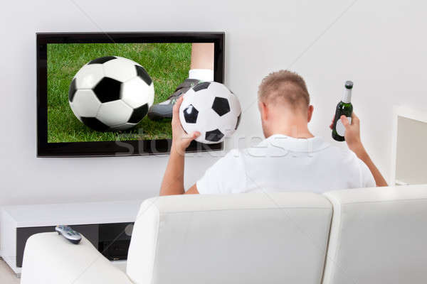 Excited soccer fan watching a game on television Stock photo © AndreyPopov