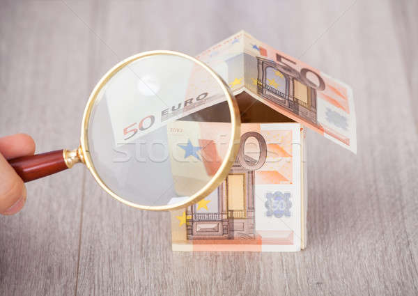 Fingers Holding Magnifying Glass To Analyze Euro House Stock photo © AndreyPopov