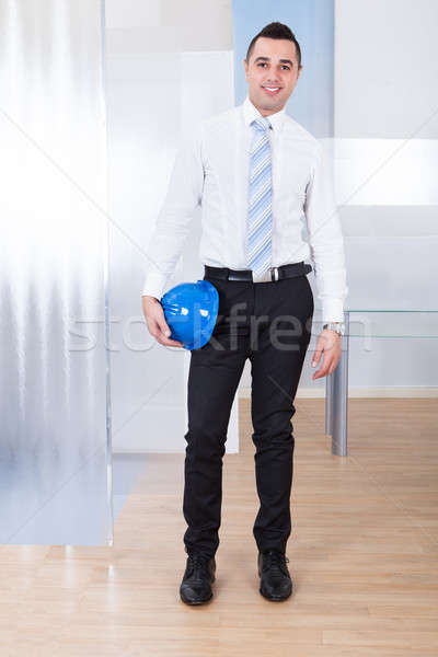 Male Architect Holding Hardhat In Office Stock photo © AndreyPopov
