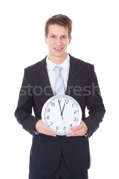 Businessman Holding Clock Over White Background Stock photo © AndreyPopov
