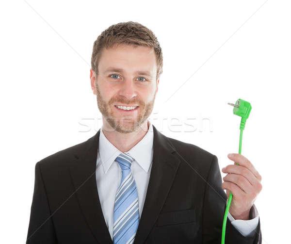 Happy Businessman Holding Green Electric Plug Stock photo © AndreyPopov