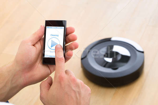 Person Using Remote Control Of Robotic Vacuum Cleaner Stock photo © AndreyPopov