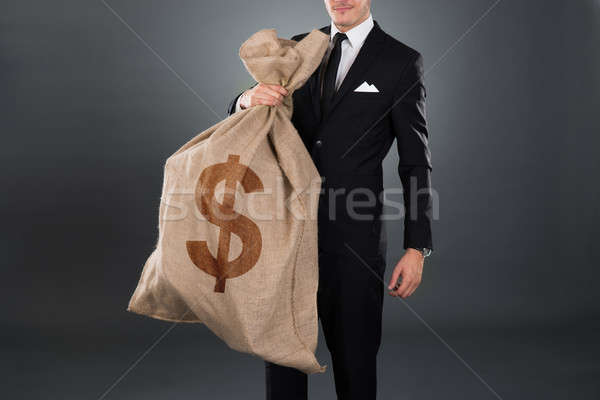Businessman Carrying Sack With Dollar Sign Stock photo © AndreyPopov