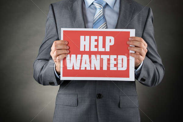 Businessman Holding Help Wanted Placard Stock photo © AndreyPopov