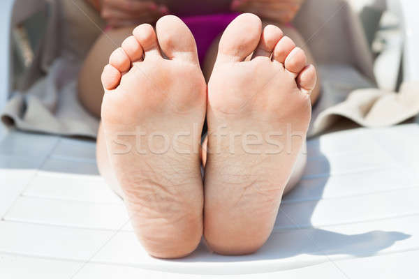 Woman's Bare Feet Tanning At Resort Stock photo © AndreyPopov