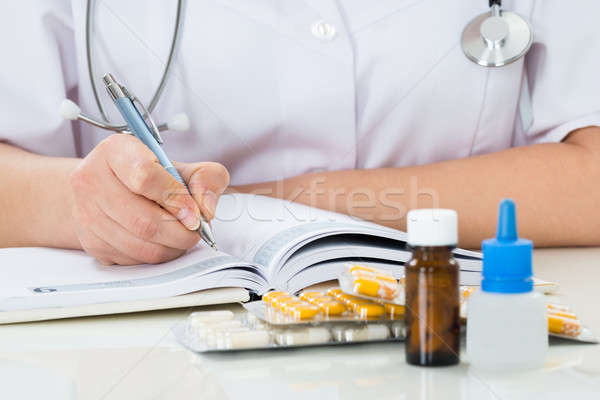 Doctor Writing Prescription On Clipboard Stock photo © AndreyPopov
