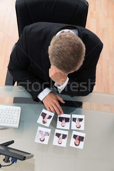 Imprenditore guardando fotografia giovani desk ufficio Foto d'archivio © AndreyPopov