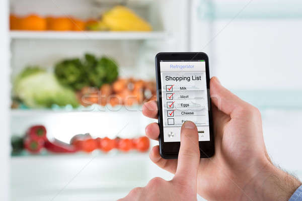 Person Hands Marking Shopping List On Mobile Phone Display Stock photo © AndreyPopov
