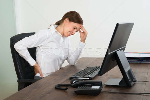 Businesswoman Suffering From Backache And Headache Stock photo © AndreyPopov