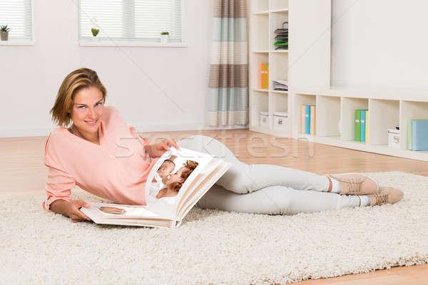 Donna guardando photo album sorridere soggiorno Foto d'archivio © AndreyPopov