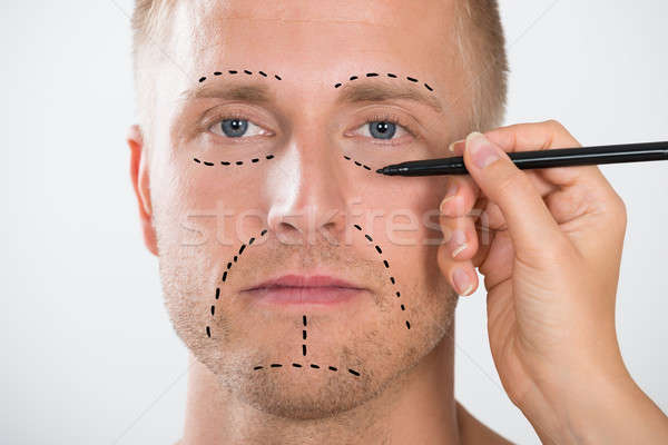 Man's Face With Correction Line Drawn By Person's Hand Stock photo © AndreyPopov